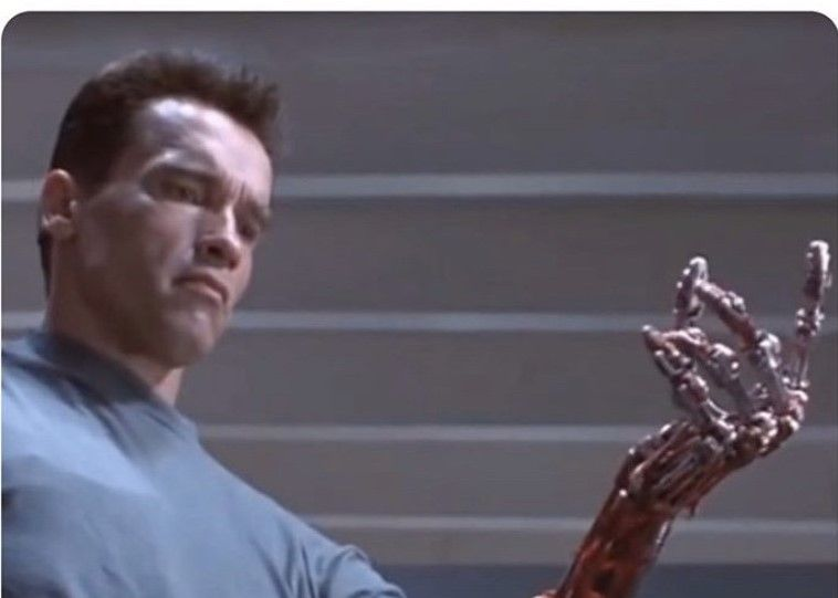 57-times-in-one-day-above-a-still-of-arnold-schwarzenegger-looking-at-his-terminator-cyborg-hand.jpg